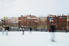Humans on rink. Blurred human figures skating on ice-rink in urban environment Royalty Free Stock Image