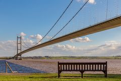 Humber Bridge, East Riding of Yorkshire, UK. A bench on the shore of the Humber Bridge in Hessle, East Riding of Yorkshire, UK - looking towards Barton-upon royalty free stock image