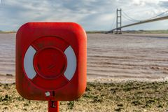 Humber Bridge, East Riding of Yorkshire, UK. A lifebelt on the shore of the River Humber, with the Humber Bridge in the background, East Riding of Yorkshire, UK stock images