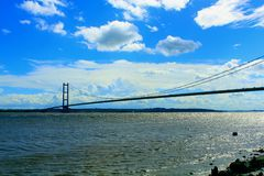Humber bridge. Hull humber bridge against bright blue sky with wispy clouds and rocky foreshore Royalty Free Stock Photo