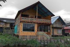 Humble a casa de madeira construída nos bancos do rio fotografia de stock royalty free