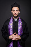 Humble catholic priest. Studio portrait on black background Royalty Free Stock Photo