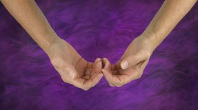 The Humble Healer. Female hands with the back of the fingers touching in a gentle gesture of hope  on a purple energy formation background Stock Photo