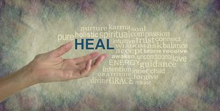 Humble Healing Words Tag Cloud. Female hand gesturing towards the word HEAL surrounded by a relevant word tag cloud on a rustic stone colored background with Royalty Free Stock Photo