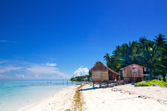 Humble homes on tropical island Stock Photo