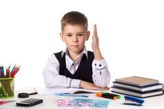 Humble o aluno excelente com a mão que senta-se acima na tabela no fundo branco fotografia de stock royalty free