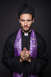 Humble priest with Christian Cross. Studio portrait on black background Stock Photos