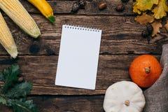 Humeur d'automne : carnet, potirons et maïs blancs avec des feuilles de jaune sur un fond en bois images libres de droits