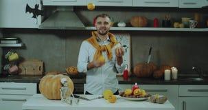 Humeur de Halloween sur la cuisine, un homme jonglant avec la mini orange devant l'appareil-photo, homme élégant, bonne humeur banque de vidéos