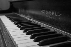 Humeurige oude piano in zwart-wit stock fotografie