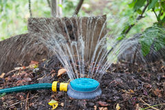 Humidification compost pile using sprinkler. Humidification compost pile using the spray, preparation of organic fertilizers Royalty Free Stock Images