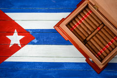 Humidor with cigars over Cuban flag background. Humidor with cigars and Cuban flag painted in background Royalty Free Stock Images