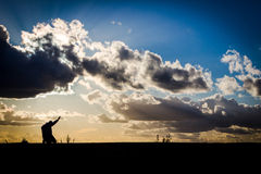 Humility before God. Man kneeling in prayer before a dramatic sky Royalty Free Stock Photos