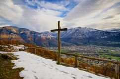 Humility - mountain view. View on cross with mountains (Alps of Ticino) in background and dramatic clouds. Footprints in first snow. Monte Carasso, Ticino Stock Photos