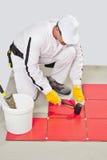 Hummer de goma del uso del trabajador para el ajusment de los azulejos Fotografía de archivo libre de regalías