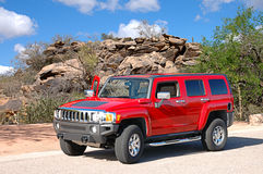 Hummer in desert setting. Beautiful red Hummer parked in a beautiful desert setting with natural rocks in the background Stock Photo