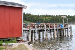 Hummerfallen und -bojen auf hölzernem Pier Stockfoto