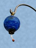 Hummingbird feeder. A close up view of a blue drop hummingbird feeder suspended from a metal hanger Stock Images
