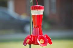 Hummingbird feeder full of nectar on a sunny day. A brilliant red hummingbird feeder for birds in for the spring Stock Photos
