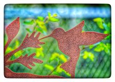 Hummingbird statue in garden has spiderwebs on it, and colorful spring growth in background. stock photography