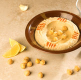 Hummous. Bowl of Hummus with raw chickpeas and lime wages Stock Photography