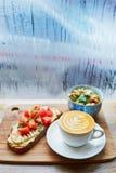 Hummus和蕃茄三明治、沙拉和新鲜的热的热奶咖啡咖啡 免版税库存照片