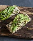 Hummus和鲕梨长方形宝石三明治用芝麻和亚麻籽在一个木切板,在灰色背景 吃健康 免版税图库摄影