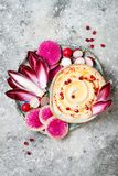 Hummus用橄榄油晒干了和辣椒粉和新鲜蔬菜:萝卜,西瓜萝卜,红色苦苣生茯,石榴 库存图片