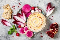 Hummus用橄榄油晒干了和辣椒粉和新鲜蔬菜:萝卜,西瓜萝卜,红色苦苣生茯,石榴 免版税库存照片