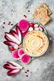 Hummus用橄榄油晒干了和辣椒粉和新鲜蔬菜:萝卜,西瓜萝卜,红色苦苣生茯,石榴 图库摄影