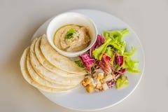 Hummus με tortillas σε έναν άσπρο πίνακα στοκ εικόνα