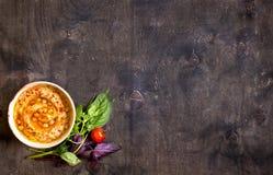 Hummus на плите с томатами и травами вишни на темном woode Стоковая Фотография RF