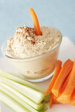 Hummus. In a clear bowl with carrots and celeri royalty free stock images