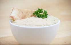 Hummus. White Bowl of Hummus on a Butcher Block Table Royalty Free Stock Photo