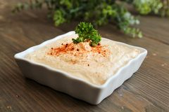 Hummus. With paprika in a white container on a wooden table stock photos