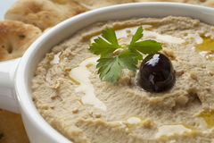Hummus. Topped with olive oil, sesame seeds, parsley and an olive, served with Lebanese bread royalty free stock image