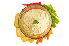 Hummus. Bowl of hummus dip with vegetables and crackers, isolated on white stock image