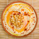 Hummus. Large bowl of hummus garnished with chickpeas, red sweet pepper and olive oil. made at home royalty free stock images