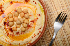 Hummus. Large bowl of hummus garnished with chickpeas, red sweet pepper and olive oil. made at home royalty free stock image