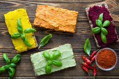 Hummus appetizer, tasty vegetarian snack. Paprika, avocado and curcuma flavour. Tasty vegitarian snacks, assortment of hummus, spread on diet bread on brown royalty free stock images