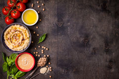 Hummus background. Bowl with hummus, chickpea, tahini, olive oil, sesame seeds, cherry tomatoes and herbs on dark rustic wooden background. Space for text. Food royalty free stock photography
