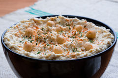 Hummus in black bowl Stock Image