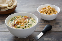 Hummus in bowl on rustic wood Stock Images