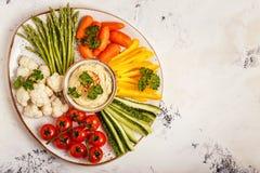 Hummus caseiro saudável com os legumes frescos sortidos Foto de Stock