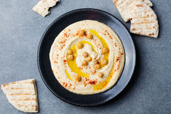 Hummus, chickpea dip, with spices and pita, flat bread in a black plate. Top view Royalty Free Stock Photography