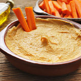 Hummus. Closeup of an earthenware bowl with appetizing hummus on a rustic wooden table royalty free stock image