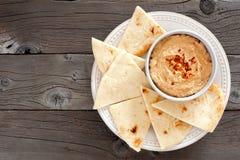 Hummus com pão do pão árabe em uma placa, acima da vista sobre a madeira Foto de Stock Royalty Free