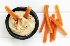 Hummus con la opinión superior de los palillos de zanahoria Imagen de archivo