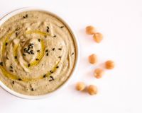 Hummus in a cup with chickpeas isolated on white. Background, with black sesame seeds and some extra virgin olive oil on top Royalty Free Stock Photos