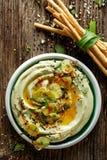 Hummus della fava, con l'aggiunta di olio d'oliva, della polvere della paprica, della menta fresca e dei semi di sesamo Fotografie Stock Libere da Diritti